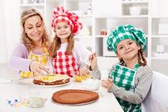 Gosses et leur mère effectuant un gâteau Photos libres de droits