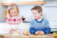 Gosses faisant des biscuits cuire au four Photos libres de droits
