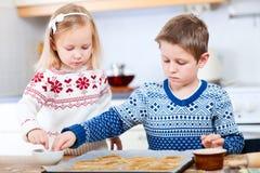 Gosses faisant des biscuits cuire au four Images libres de droits