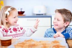 Gosses faisant des biscuits cuire au four Photographie stock libre de droits