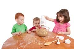 Gosses faisant des biscuits cuire au four avec le mélangeur électrique Images libres de droits