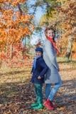 Gosses heureux ayant l'amusement dans le stationnement d'automne Photo stock