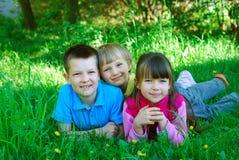Gosses heureux dans l'herbe Photos libres de droits