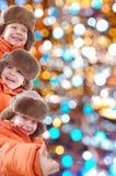 Gosses heureux de l'hiver contre les lumières colorées Photographie stock libre de droits
