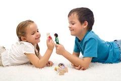 Gosses heureux - garçon et fille - jouant sur l'étage Image stock