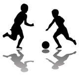 Gosses jouant au football d'isolement sur le blanc Photos stock