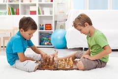 Gosses jouant aux échecs dans leur chambre Photo stock