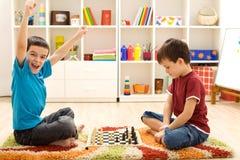 Gosses jouant aux échecs - a juste saisi un gage Photos stock