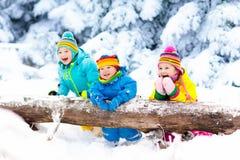 Gosses jouant dans la neige Jeu d'enfants dehors en chutes de neige d'hiver Photographie stock libre de droits
