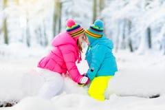 Gosses jouant dans la neige Jeu d'enfants dehors en chutes de neige d'hiver Image stock
