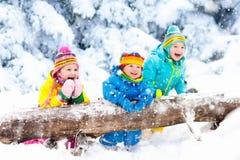 Gosses jouant dans la neige Jeu d'enfants dehors en chutes de neige d'hiver Images stock