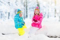 Gosses jouant dans la neige Jeu d'enfants dehors en chutes de neige d'hiver Photos libres de droits