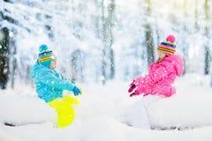 Gosses jouant dans la neige Jeu d'enfants dehors en chutes de neige d'hiver Images libres de droits