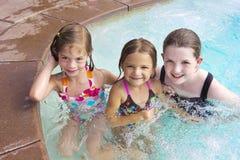 Gosses jouant dans la piscine ensemble Image stock