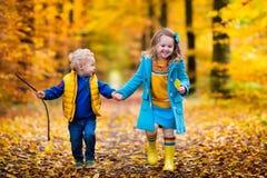 Gosses jouant en stationnement d'automne Photos stock
