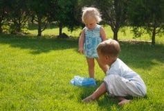 Gosses jouant sur l'herbe verte photo stock