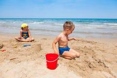 Gosses jouant sur la plage Photos libres de droits