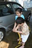 Gosses lavant le véhicule photos stock