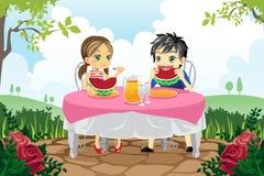 Gosses mangeant la pastèque en stationnement Image libre de droits