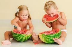 Gosses mignons drôles mangeant la pastèque Image libre de droits