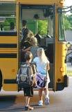 Gosses montant dans l'autobus scolaire photos stock