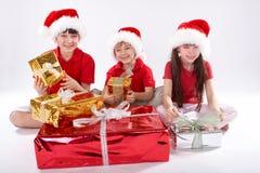 Gosses ouvrant des cadeaux de Noël Image libre de droits