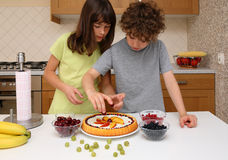 Gosses préparant le gâteau fruité images libres de droits