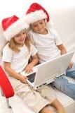 Gosses recherchant des cadeaux de Noël en ligne Images libres de droits
