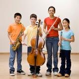 Gosses retenant le saxophone, le violoncelle, la cannelure et le clarinet Image stock