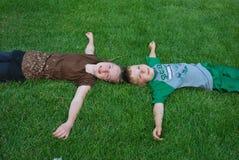 Gosses s'étendant sur l'herbe Photos libres de droits