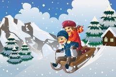 Gosses sledding dans la neige Photographie stock libre de droits