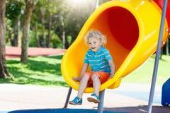 Gosses sur la cour de jeu Jeu d'enfants en parc d'été Photo stock