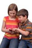 Gosses texting photos libres de droits