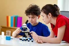 Gosses utilisant le microscope Image stock
