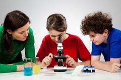 Gosses utilisant le microscope Images libres de droits