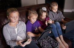 Gosses utilisant les dispositifs mobiles Photo libre de droits