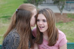 Gossip. Teenage girls are sitting outdoors whispering secrets to each other Royalty Free Stock Photo