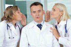 Gossip. Portrait of surprised male clinician between two gossiping women royalty free stock image