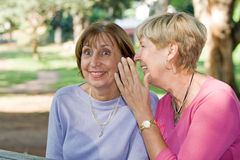 Gossip. Two senior elderly women sitting in the park and gossiping. telling a secret to another Royalty Free Stock Photos