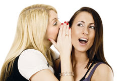 Gossip. Two young females together, one whispering into the others ear stock photo