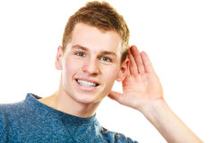 Gossip boy with hand behind ear spying. Gossip. Young man holding hand to ear listening isolated on white background stock photography