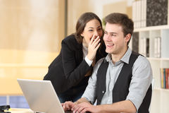 Gossip businesspeople telling secrets. Gossip businesswoman telling secrets to the ear of a businessman sitting on a desktop at office Royalty Free Stock Photo