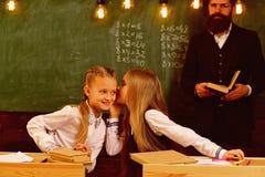 Gossip che bisbiglia, bambine che bisbigliano gossip alla lezione della scuola un sussurro del gossip di due amici di ragazze Gos fotografia stock libera da diritti