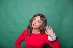 Gossip concept. Colorful studio portrait of pretty young woman with palm near her ear. pretty woman in red dress holds stock images