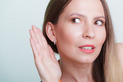 Gossip girl eavesdropping with hand to ear. Woman overhearing listening to rumors. Spying and secret concept royalty free stock images