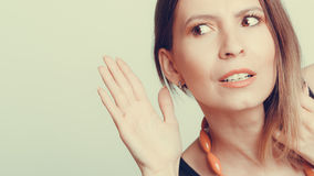 Gossip girl eavesdropping with hand to ear. Woman overhearing listening to rumors. Spying and secret concept. Instagram filter royalty free stock photo