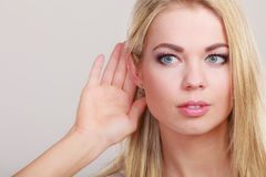 Gossip girl with hand behind ear spying Royalty Free Stock Image
