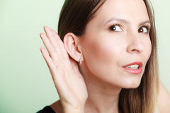 Gossip girl with hand behind ear spying. Stock Photos