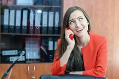 Gossip girl. A woman in a red business suit is smiling and talking on the phone in the office Stock Photos