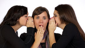 Gossip Girls. Three teenage girls gossiping about something with great interest and expression stock photo